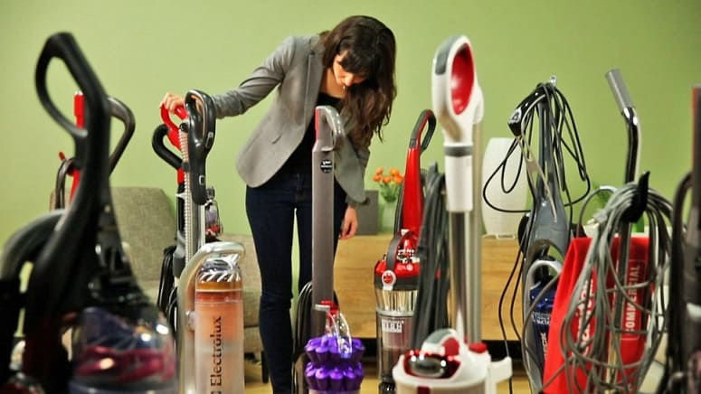 Woman Looking At Different Vaccum Cleaners