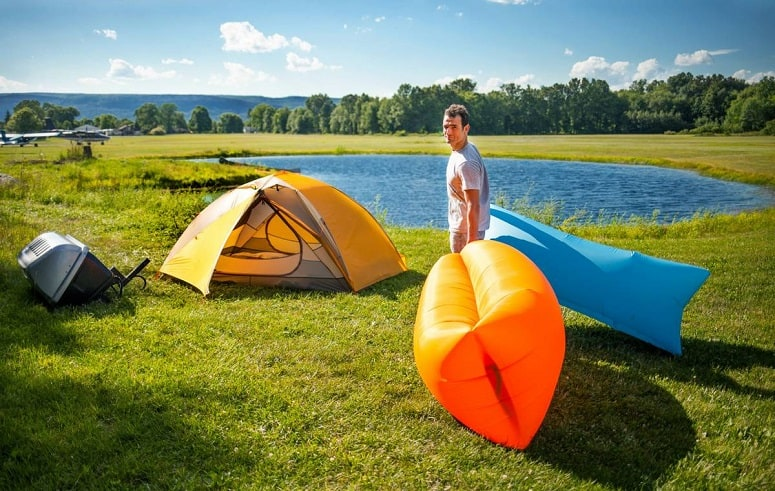 Man Carrying Two Inflatable Lounger
